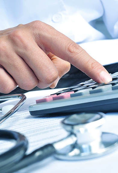 closeup of a caucasian healthcare professional wearing a white coat calculates on an electronic calculator