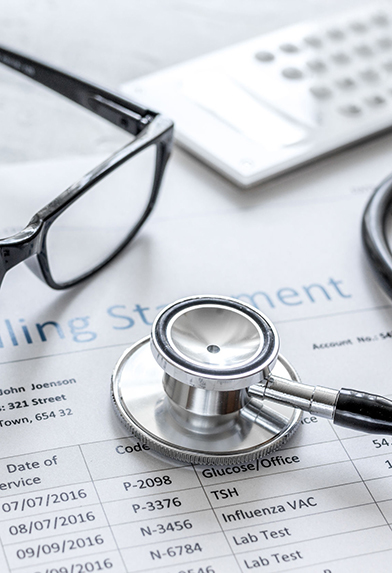 medical billing statement with stethoscope and glasses on stone desk background